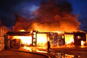 Großbrand einer Halle mit heftigem Feuer und Löscharbeiten der Feuerwehr.