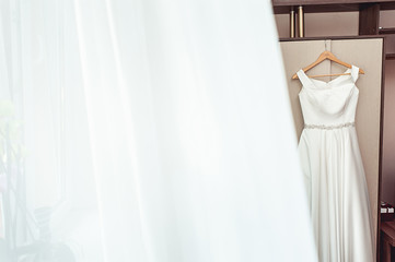 Simple white wedding dress on the rack at the wardrobe