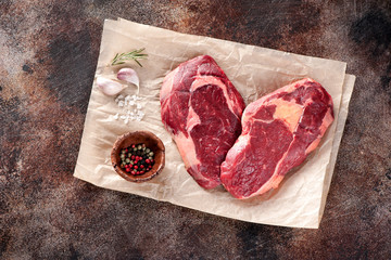 Wall Mural - Raw fresh meat Ribeye Steak heart shape, garlic, pepper and rosemary on brown paper