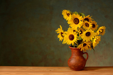 Sunflower in a ceramic vase on a wooden table