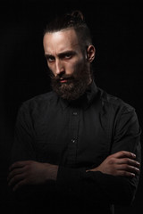 Studio portrait of a handsome man with a beard in the black shirt