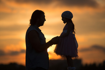 the girl with the dad walking in sunset silhouette