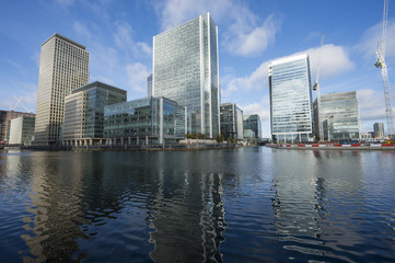 Scenic water view of the modern skyline of London reflecting in the River Thames on a bright day