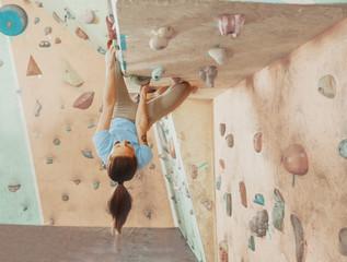 Climber sportswoman training indoor.