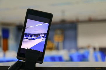smartphone take a photo on screen of the meeting room business select focus with shallow depth of field.