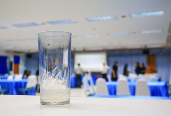 ice water in glass in seminar conference room background. select focus with shallow depth of field