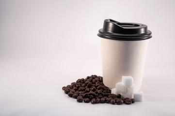 Roasted coffee beans. Take away coffee mug. sugar cubes. Background.