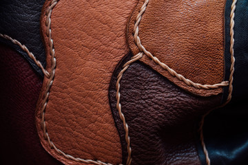 A fragment of a leather bag and a purse made of multi-colored pieces. White leather stitching.