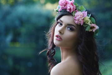 Romantic Woman with Peony Flowers Outdoors. Spring Beauty Portrait