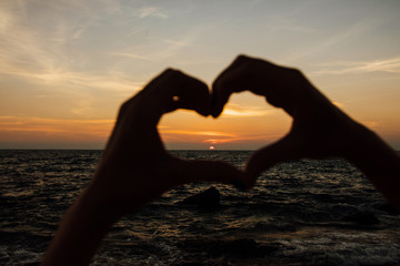 Silhouette hand in heart shape with sunrise in the middle and beach background
