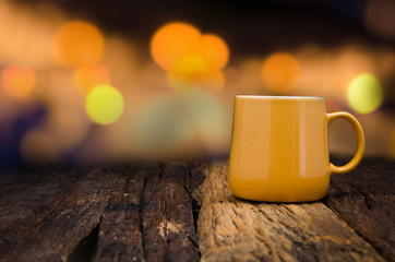 Yellow ceramic empty mug on old wooden table top with copy space and bokeh background