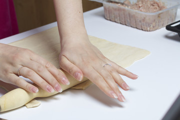 Stages of preparation of meat glomeruli. A woman rolls out the dough. Next to the table is a stuffing and lie tools.