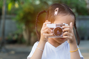 Little child girl take film camera.