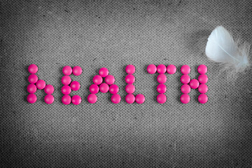 Word health made by pink pills and white feather on the grey background