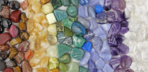 Healing Chakra Crystals Banner - Chakra colored tumbled healing stones laid in neat color coordinated rows creating a crsytal healing background