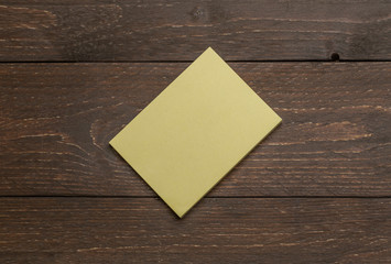 Yellow pack pile of stickers on the dark wooden rustic background for advertising diagonal mockup template