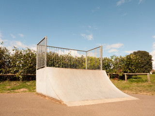 An Empty and Unused Ramp Half Pipe at the Skate Park in the Country Park in the UK Shining in the Sunlight of the Day and with A Shrub Hedge Behind the Bars Protecting it Fenced