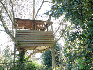 A Wooden Tree House in Someone's Back garden and Yard with A Roof and With Trees Next to It in the Uk