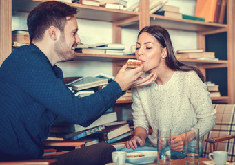 Dating in cafeteria. Young couple drinking coffee and eating cake in cafeteria. Education, dating, relationships, lifestyle concept