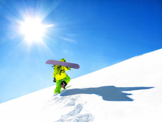 Snowboarder with board going to freeride at blue sky background
