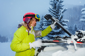 Young woman fastening skis on the roof of car