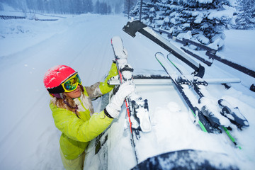 Female skier fastening skis to car roof's rails