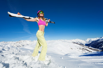 Active woman standing with skies on her shoulders