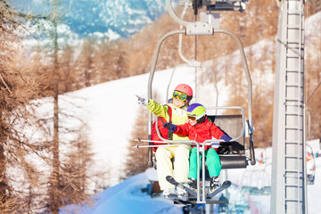 Active woman and her kid son lifting on chairlift