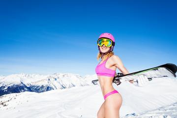 Woman in bikini standing with skis on a snowy peak