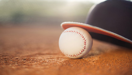 Baseball cap and baseball ball on field, copy space