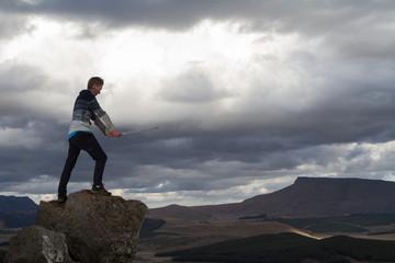 Boy hero with sword in landscape