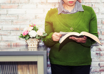 woman is  reading bible in front of white brick wall near book cabinet