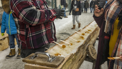 Maple taffy sugar candy A street vendor selling maple toffee made of hot maple syrup poured on snow.