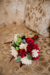 A wedding bouquet of roses and chrysanthemums on the sofa.