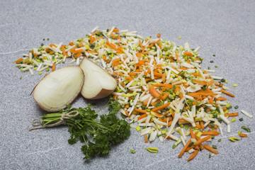 suppengemüse gestreut auf granitarbeitsplatte mit zwiebel und petersilie