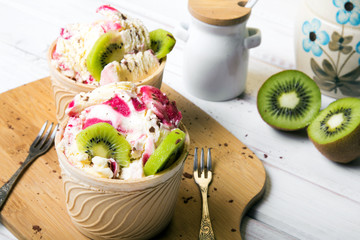 Delicious ice cream in a cup with tasty fruits