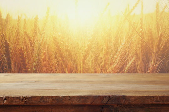 wood board table in front of field of wheat on sunset light