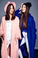 fashion portrait of two smiling brunette women models in summer casual hipster overcoat posing on gray background. Full length