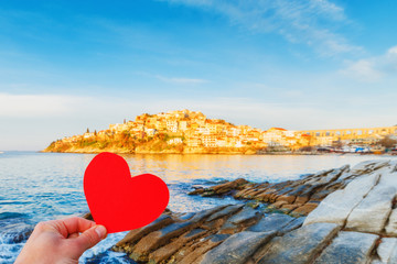 I love Greece concept. Person keep paper red heart in hand at greek medieval summer resort city Kavala. Sunrise scenery.