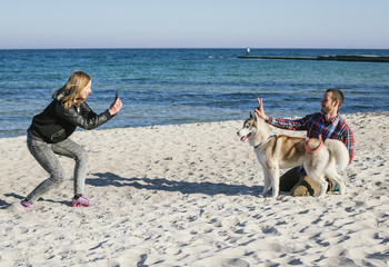 Young caucasian couple doing photo with siberian husky dog on sea beach