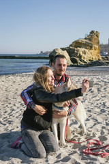 Young caucasian couple on beach doing selfie on smart phone with siberian husky dog