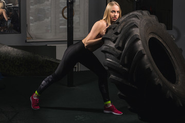Fit female flipping tire at the gym.