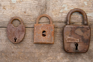 Three old rusty locks on wooden background