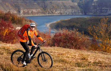 Cyclist in orange jacketr riding bike on the hill under river against beautiful landscape.