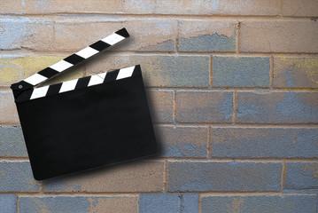 Ciak da regista su muro con mattoni colorati. Sfondo per presentazione di filmati. Concetto di partenza, start up, inizio, idea iniziale.