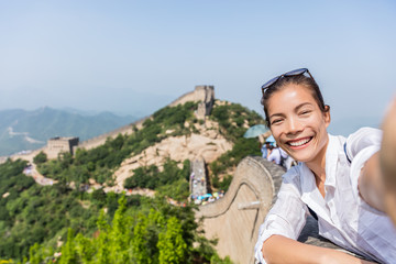 Wall Mural - Selfie. Tourist at Great Wall of china excited and happy having fun at famous Badaling during travel holidays at Chinese tourist destination. Woman tourist taking picture during Asia vacation.