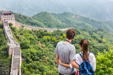 Happy couple enjoying view of Great wall of china landscape near Beijing city. Asia travel. Tourists relaxing together in summer.