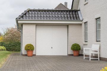 Garage mit Einfahrt und weißem Tor