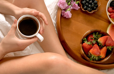 Woman eating breakfast and drinks coffee in the bed.