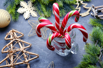 Christmas candy canes in jar and decor on gray background